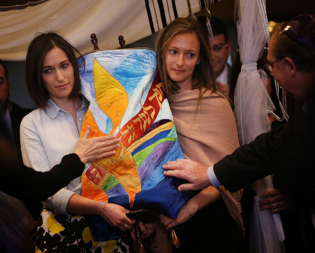 Adina Weinberg (left) and Jordana Weinberg, daughters of Rabbi Stefan Weinberg, carry the torah into the synagogue  that was made specifically for Congregation Anshai Torah in Plano.