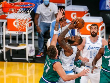 Los Angeles Lakers' LeBron James (23) goes to the basket while defended by Dallas Mavericks' Luka Doncic (77) during the first half of an NBA basketball game Friday, Dec. 25, 2020, in Los Angeles.