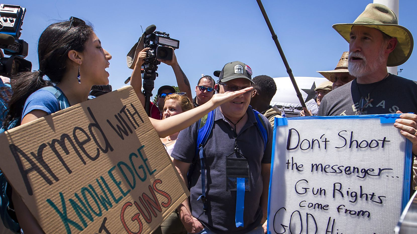 Gun rights advocates Drew Deal of Dallas (right) discusses the second amendment with a gun control advocate who would not give her name as dueling groups demonstrated outside Dallas City Hall during the NRA Annual Meeting & Exhibits at the Kay Bailey Hutchison Convention Center on Saturday, May 5, 2018, in Dallas. (Smiley N. Pool/The Dallas Morning News)