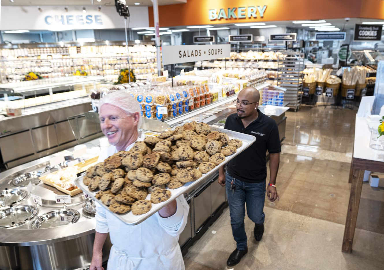 Pascal Wattiau, bakery manager, left, carries a tray of fresh cookies as he's followed by base operator Demetrius Fleming. The two men helped other employees prepare the Central Market at Preston Road and Royal Lane for their re-grand Opening, on Wednesday.