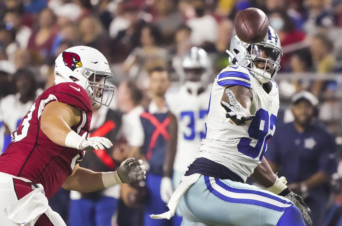 Dallas Cowboys defensive end Dorance Armstrong (92) tries to intercept a tipped ball against Arizona Cardinals offensive lineman Marcus Henry (53) during the second quarter of an NFL football game at State Farm Stadium on Friday, Aug. 13, 2021, in Glendale, Ariz.