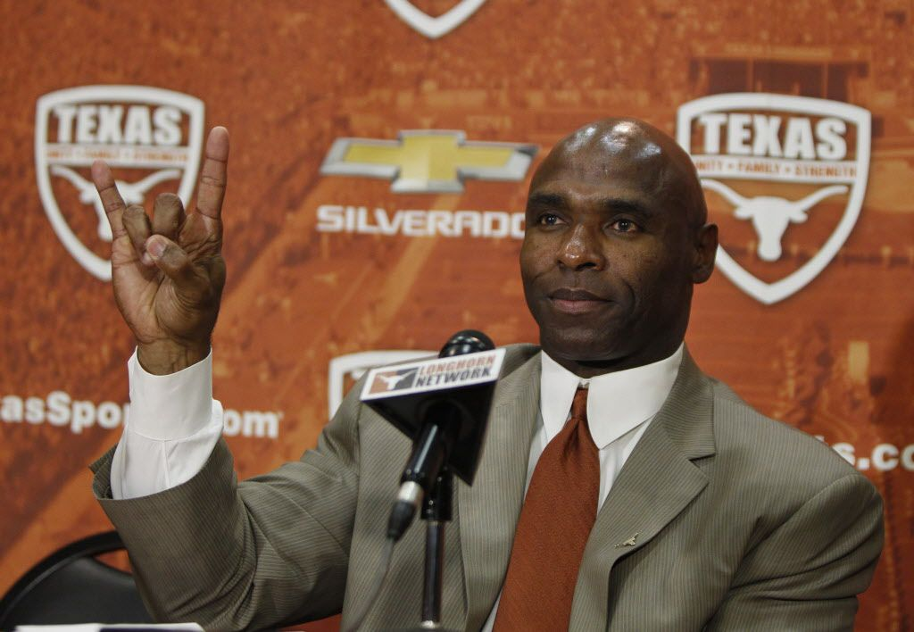 """AUSTIN, TX - JANUARY 6: The University of Texas Longhorns new head football coach Charlie Strong from Louisville flashes the """"Hook 'Em Horns"""" sign after being introduced during a press conference January 6, 2014 at Darrell K."""