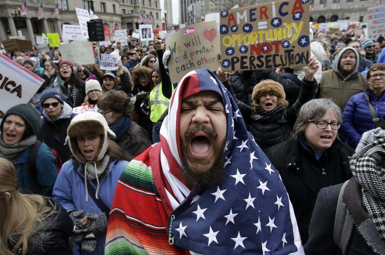 El residente de Boston Izzy Berdan (al centro) se cubre con una bandera de Estados Unidos mientras corea lemas con otros manifestantes durante una manifestación contra el decreto del presidente Donald Trump que prohíbe el ingreso en Estados Unidos a ciudadanos de siete naciones predominantemente musulmanes, el domingo 29 de enero de 2017, en Boston. (AP/STEVEN SENNE)