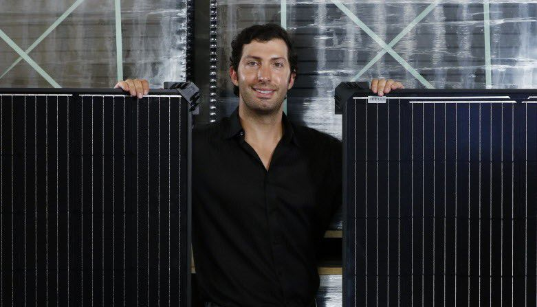 Abe Issa, CEO of Global Efficient Energy, with solar panels in the company''s warehouse in Fort Worth.