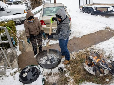 A conservation notice issued this week gave a moment of dreaded deja vu to many Texans, who are still reeling from February's devastating grid failure. In Feb. 17 file photo, an East Dallas couple who'd lost power three days earlier and were staying warm in their car cook a meal on a grille.