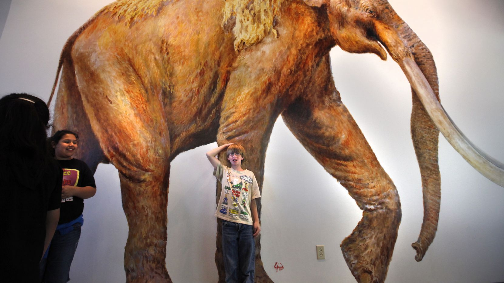 jacob Jean measures his height compared to a mural of a mammoth during their field trip to the Waco Mammoth Site in Waco, TX on May 3, 2011. At left facing camera is Melenie (cq) Juarez, also a 5th grader. Pending legislation would designate the Waco Mammoth Site a national monument through the use of private funds and limited federal oversight. ( Kye R. Lee / The Dallas Morning News )    05092011xNEWS