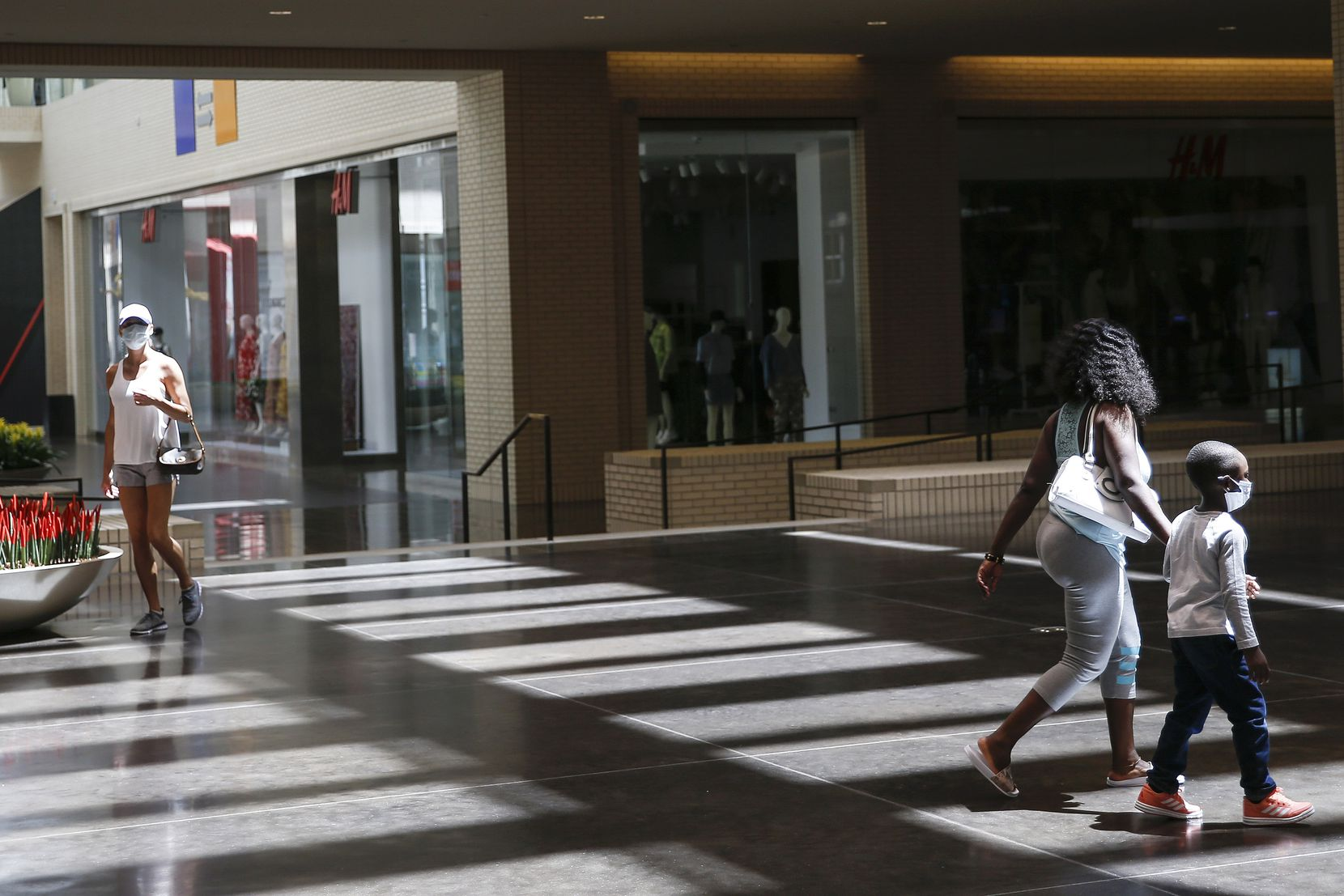 Shoppers walk through NorthPark Center mall on Friday, May 1, 2020 in Dallas, Texas. Texas Gov. Greg Abbott's executive order requiring Texans to stay at home expired on Thursday, allowing businesses to reopen under certain conditions as soon as Friday. Stores, restaurants and movie theaters may open as long as they maintain only a 25% occupancy and follow social distancing. Under those guidelines, malls can also open but food courts, play areas and interactive displays or settings must remain closed. (Ryan Michalesko/Staff Photographer)