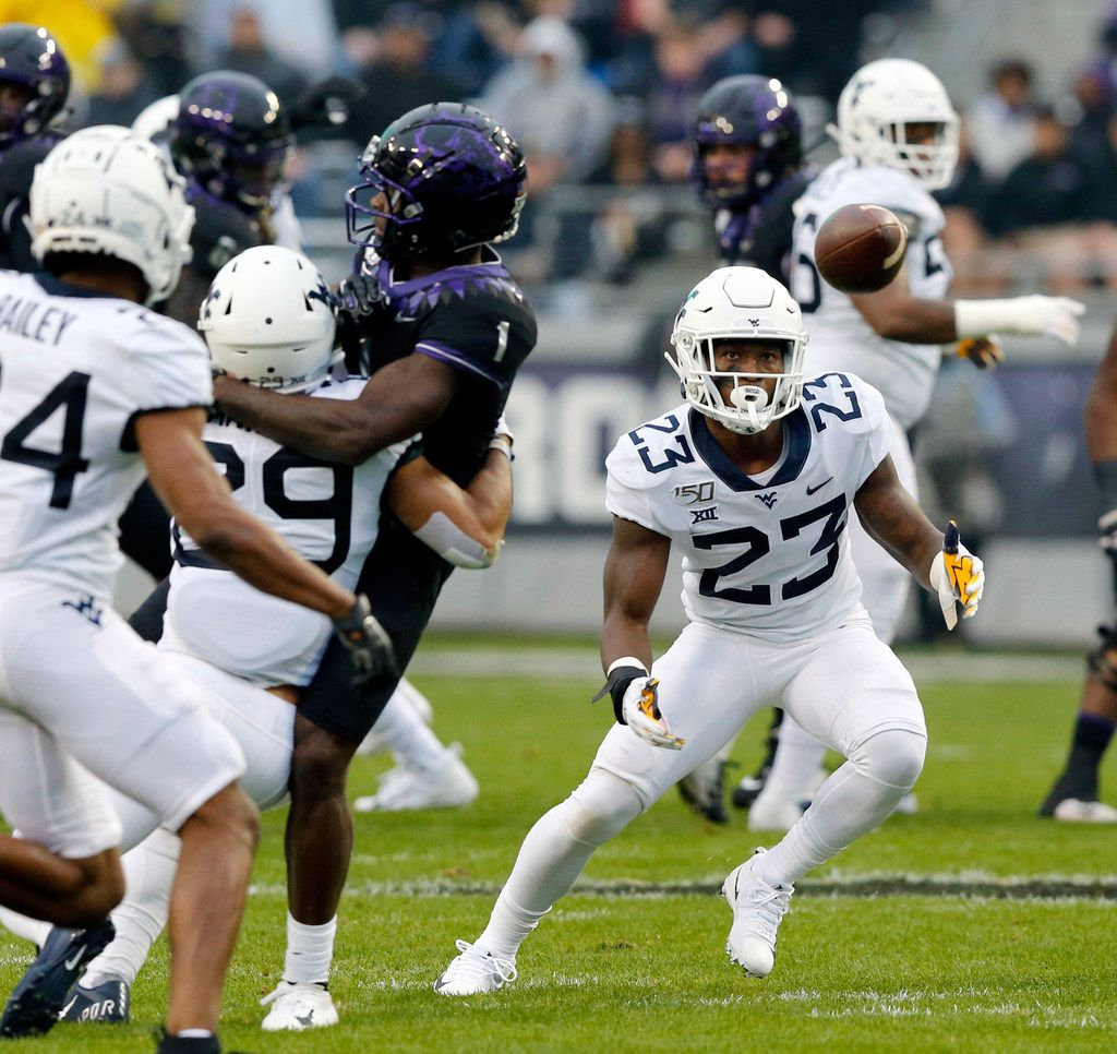 West Virginia Mountaineers safety Tykee Smith (23) eyes a tipped pass before intercepting a pass intended for TCU Horned Frogs wide receiver Jalen Reagor (1) at Amon G. Carter Stadium in Fort Worth, Friday, November 29, 2019.(Tom Fox/The Dallas Morning News)