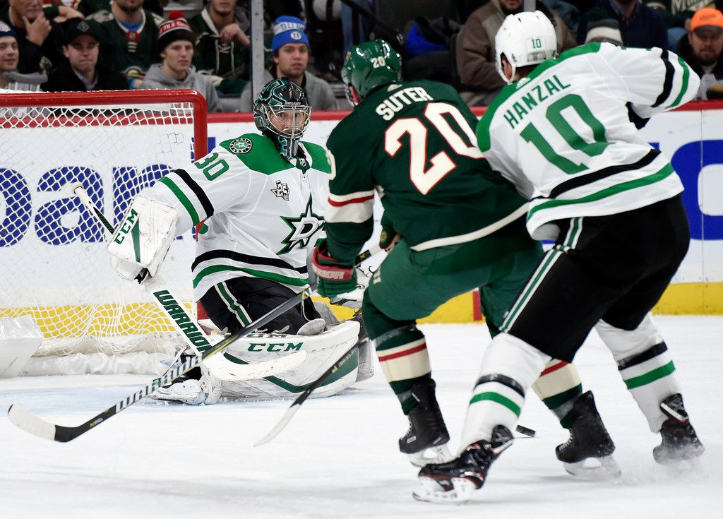 Dallas Stars goalie Ben Bishop (30) watches as center Martin Hanzal (10), of the Czech Republic, hooks Minnesota Wild's Ryan Suter (20) during the second period of an NHL hockey game Wednesday, Dec. 27, 2017, in St. Paul, Minn. Hanzal was called for a minor penalty on the play. (AP Photo/Hannah Foslien)