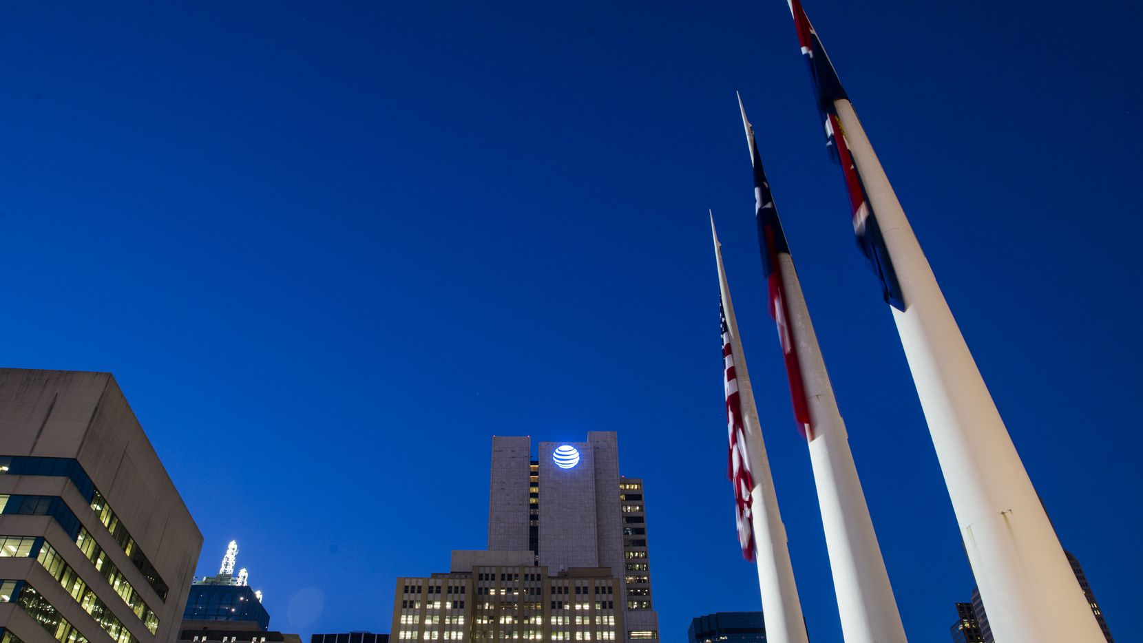 The AT&T headquarters building, surrounded by other downtown buildings and flags in front of City Hall on Monday in downtown Dallas.
