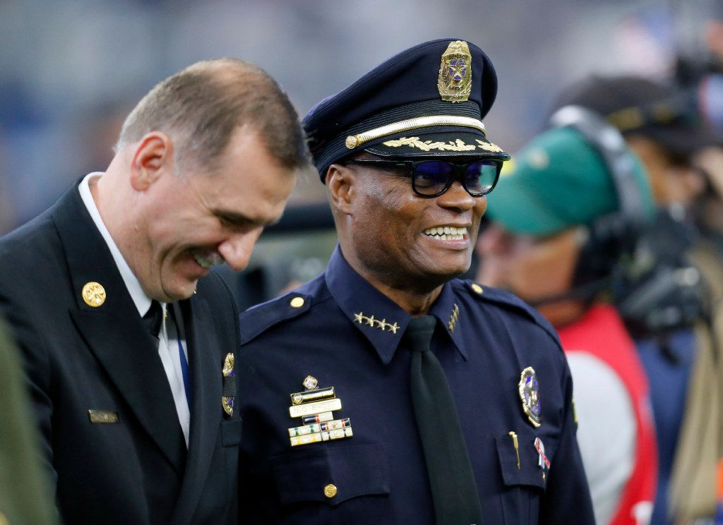 Arlington Fire Department Chief Don Crawson, left, smiles as he talks with retired Dallas Police Chief David Brown, right, as the two and others participate in a first responders appreciation ceremony during an NFL football game between the Dallas Cowboys and New York Giants on Sunday Sept. 11,  2016, in Arlington, Texas. (AP Photo/Roger Steinman)