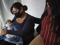 Lucy Palacios, right, 23, comforts her mother, Miriam, as she holds her 2-month-old grandson, Isaiah, at their home in northeast Dallas Tuesday. The Palacios family has faced a double loss of loved ones from COVID-19.