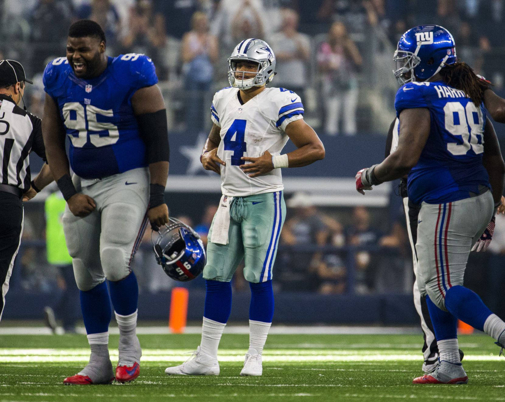 Dallas Cowboys quarterback Dak Prescott (4) watches as New York Giants defensive tackle Johnathan Hankins (95) and defensive tackle Damon Harrison (98) celebrate a 20-19 win after the clock ran out on their game on Sunday, September 11, 2016 at AT&T Stadium in Arlington, Texas.