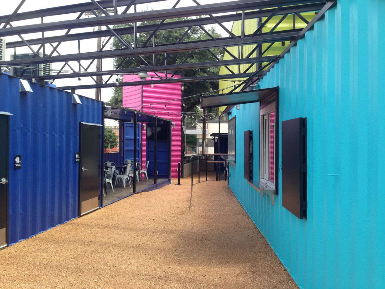 Old shipping containers have been repurposed on Akard Street outside the Lorenzo Hotel into a beverage and patio area.