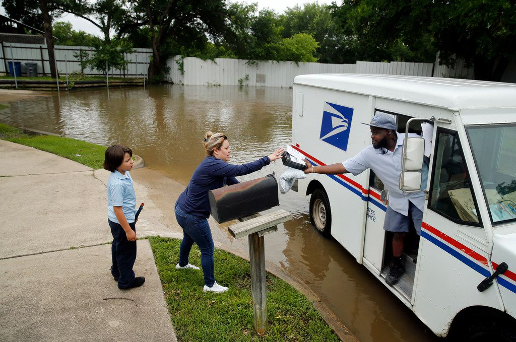 Mail carrier Terry LeRoy handed Violet Saldua and her son Jake her mail on May 9 because her driveway and mailbox are surrounded by water on Maybeth Street in West Dallas. She says her cul-de-sac floods every time there is significant rain.