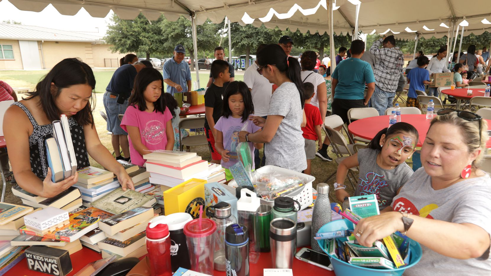 Volunteers pass out books and supplies during the Frisco Family Services Summer Lunch Grande Finale event at Bright Academy in Frisco on Aug. 2, 2019. Frisco Family Services is one of the charities involved in Give for Frisco Day.