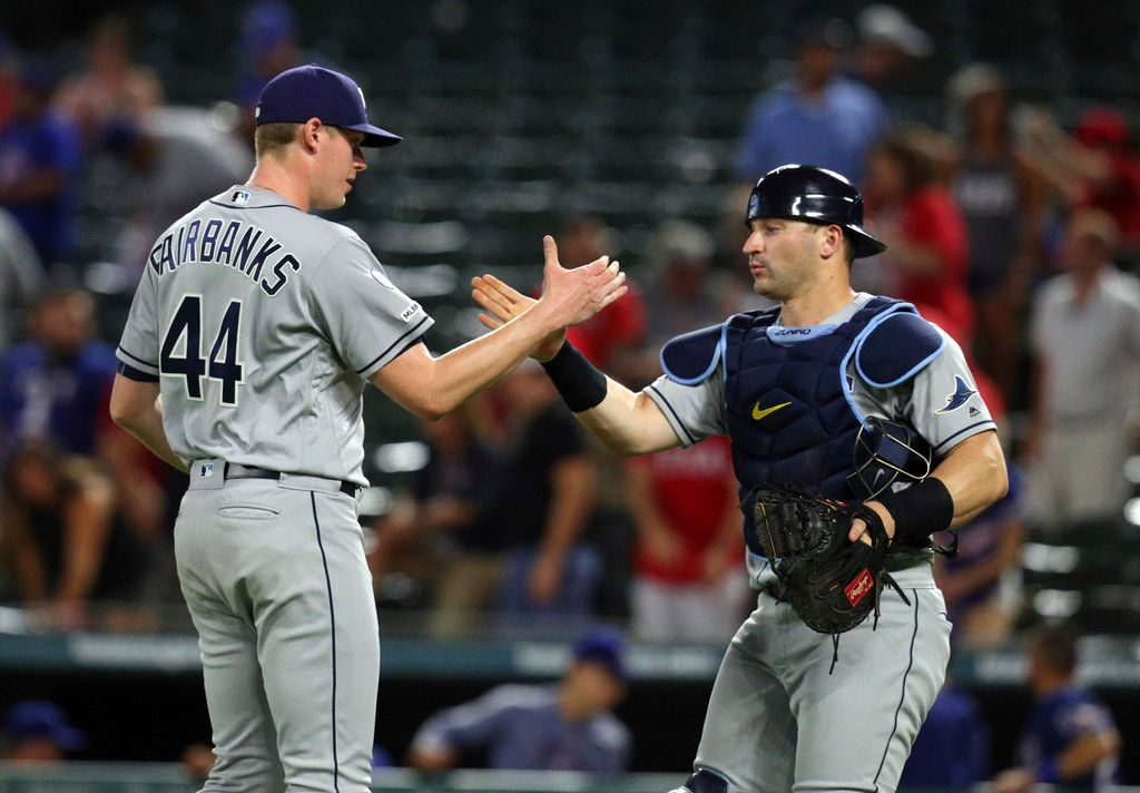 Tampa Bay Rays relief pitcher Peter Fairbanks (44) celebrates with catcher Mike Zunino (10) after the team's 5-3 win over the Texas Rangers in 11 innings in a baseball game Tuesday, Sept. 10, 2019, in Arlington, Texas. (AP Photo/Richard W. Rodriguez)