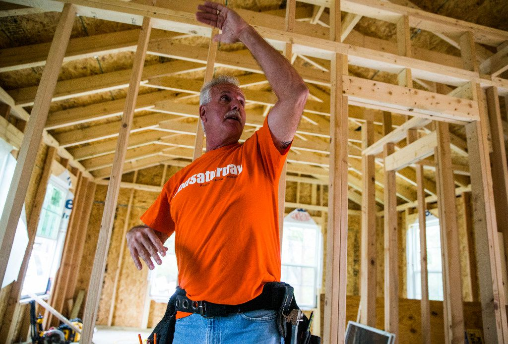Project manager Martin Evans of 2ndSaturday's 2S Industries program describes work being done on a house being rebuilt in Oak Cliff. (Ashley Landis/The Dallas Morning News)