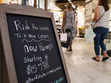 """Now hiring sign on display at the store front of """"Altar'd State"""" inside Galleria Dallas."""