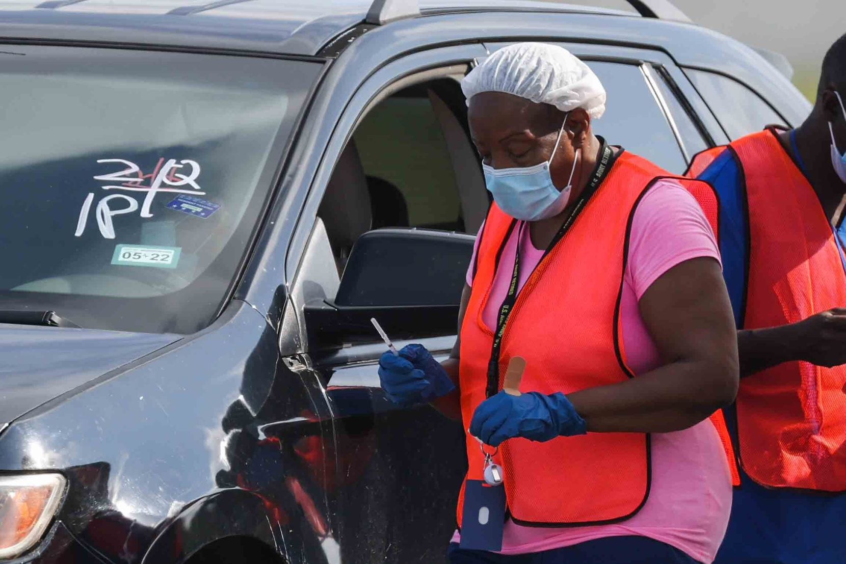 A nurse with a dose of the COVID-19 vaccine went to a vehicle where a person waited to be vaccinated in Lot 13 at Fair Park on Aug. 7, 2021.