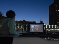 "A boy stands up through a car's sunroof to watch ""Dirty Dancing,"" at a drive-in movie held in the parking lot of the Bel Aire Diner, Wednesday, May 13, 2020, in the Queens borough of New York. Drive-in movies are seeing a resurgence across the country and the world amid the coronavirus pandemic."