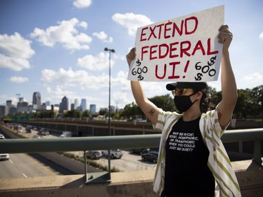 Linh Bui holds a sign as service workers and community activists hold a banner asking for the extension of federal employment benefits over North Central Expressway on July 24 in Dallas. Congress is poised to let the benefit expire on Friday.