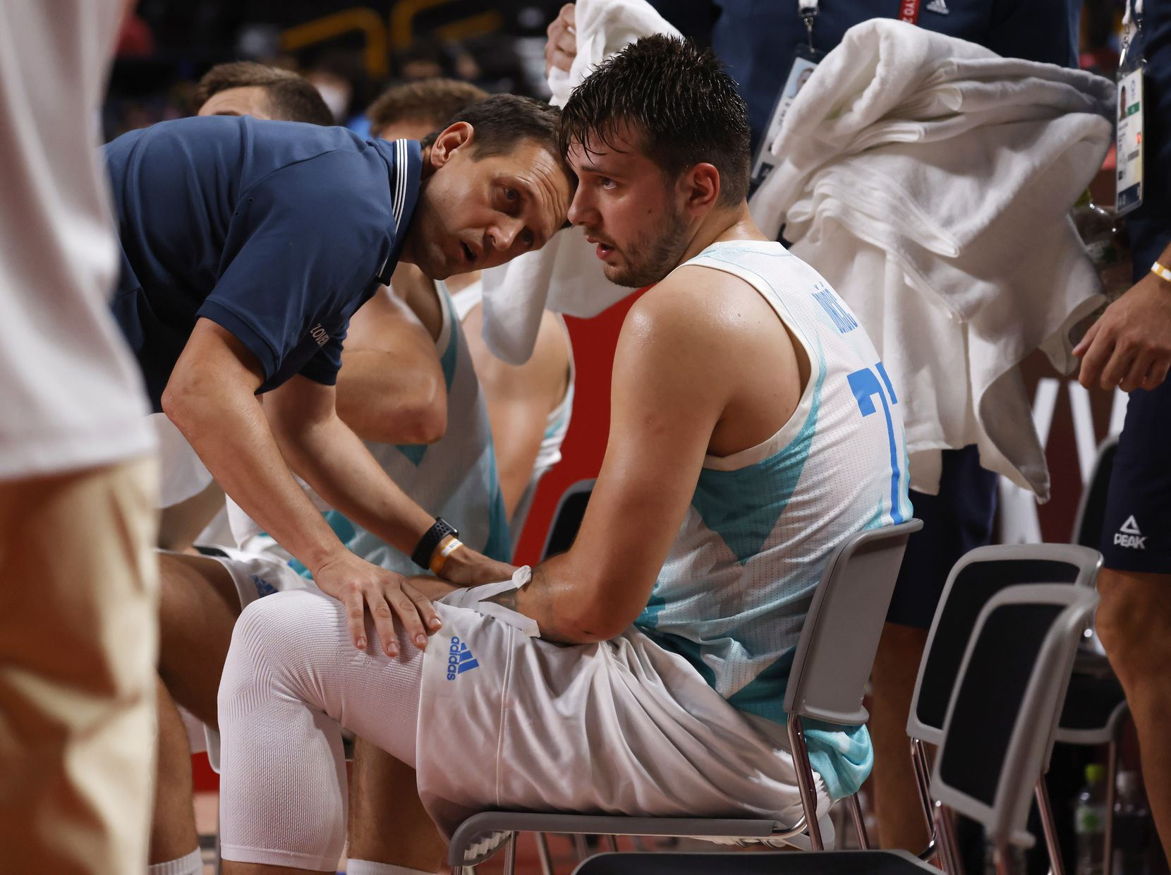 Slovenia's head coach Aleksander Sekulic consoles Luka Doncic (77) as he sits on the bench during a timeout in a game against Australia during the third quarter of play in the bronze medal basketball game at the postponed 2020 Tokyo Olympics at Saitama Super Arena, on Saturday, August 7, 2021, in Saitama, Japan. (Vernon Bryant/The Dallas Morning News)