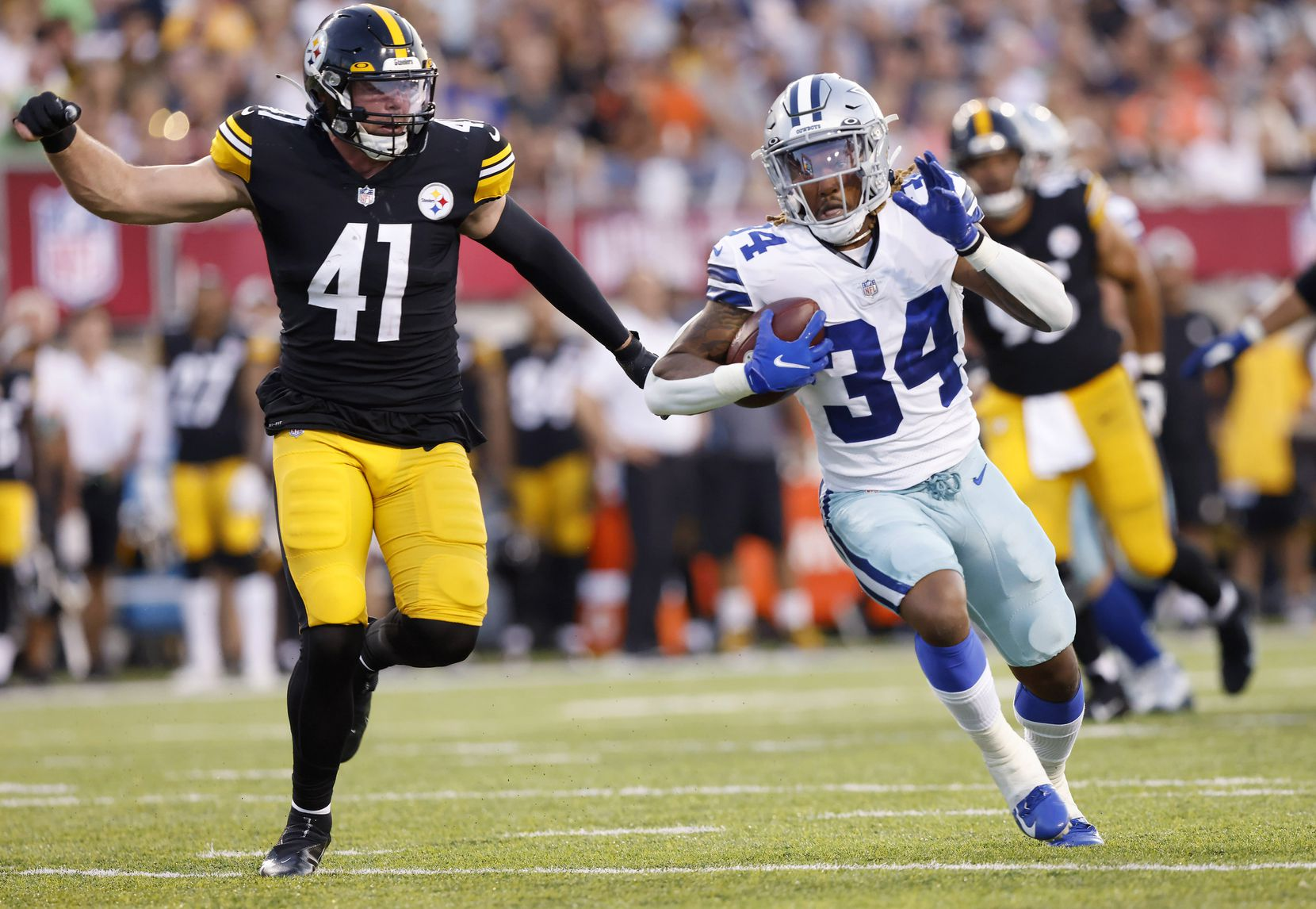 Dallas Cowboys running back Rico Dowdle (34) carries the ball against Pittsburgh Steelers linebacker Robert Spillane during the first quarter of their preseason game at Tom Benson Hall of Fame Stadium in Canton, Ohio, Thursday, August 5, 2021. (Tom Fox/The Dallas Morning News)