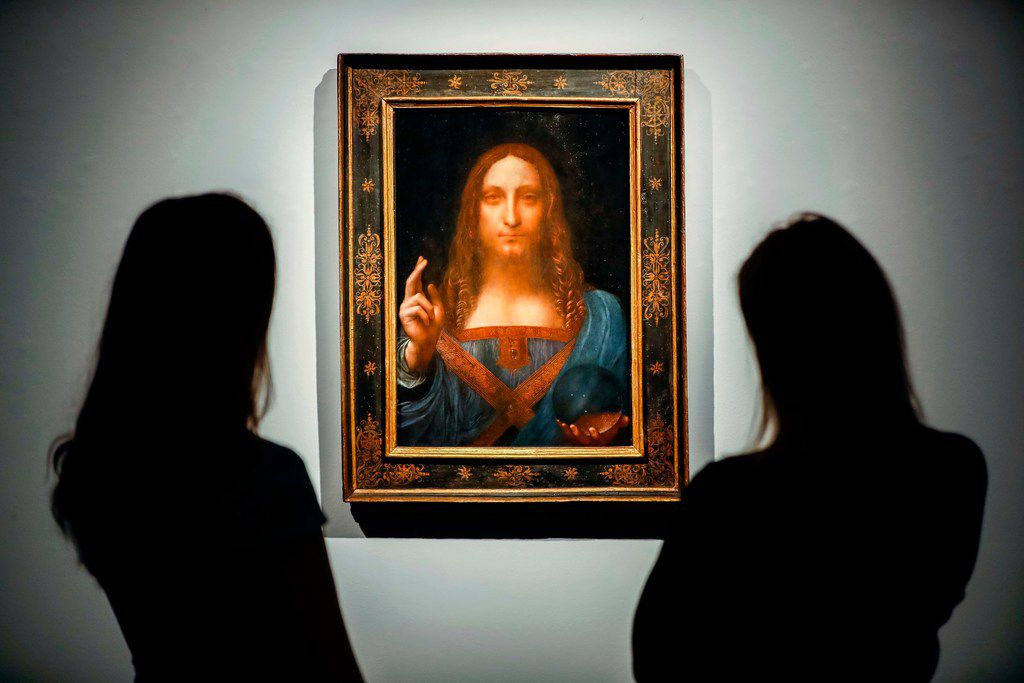 In this file photo taken on October 24, 2017, Christie's employees pose in front of a painting entitled Salvator Mundi by Italian polymath Leonardo da Vinci at a photo call at Christie's auction house in central London ahead of its sale at Christie's New York on November 15, 2017.
