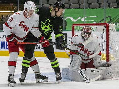 Dallas Stars left wing Roope Hintz (24) struggles against Carolina Hurricanes right wing Andrei Svechnikov (37) to attempt a score past goaltender Alex Nedeljkovic (39) during the first period of play in a game at the American Airlines Center on Saturday, Feb. 13, 2021, in Dallas.
