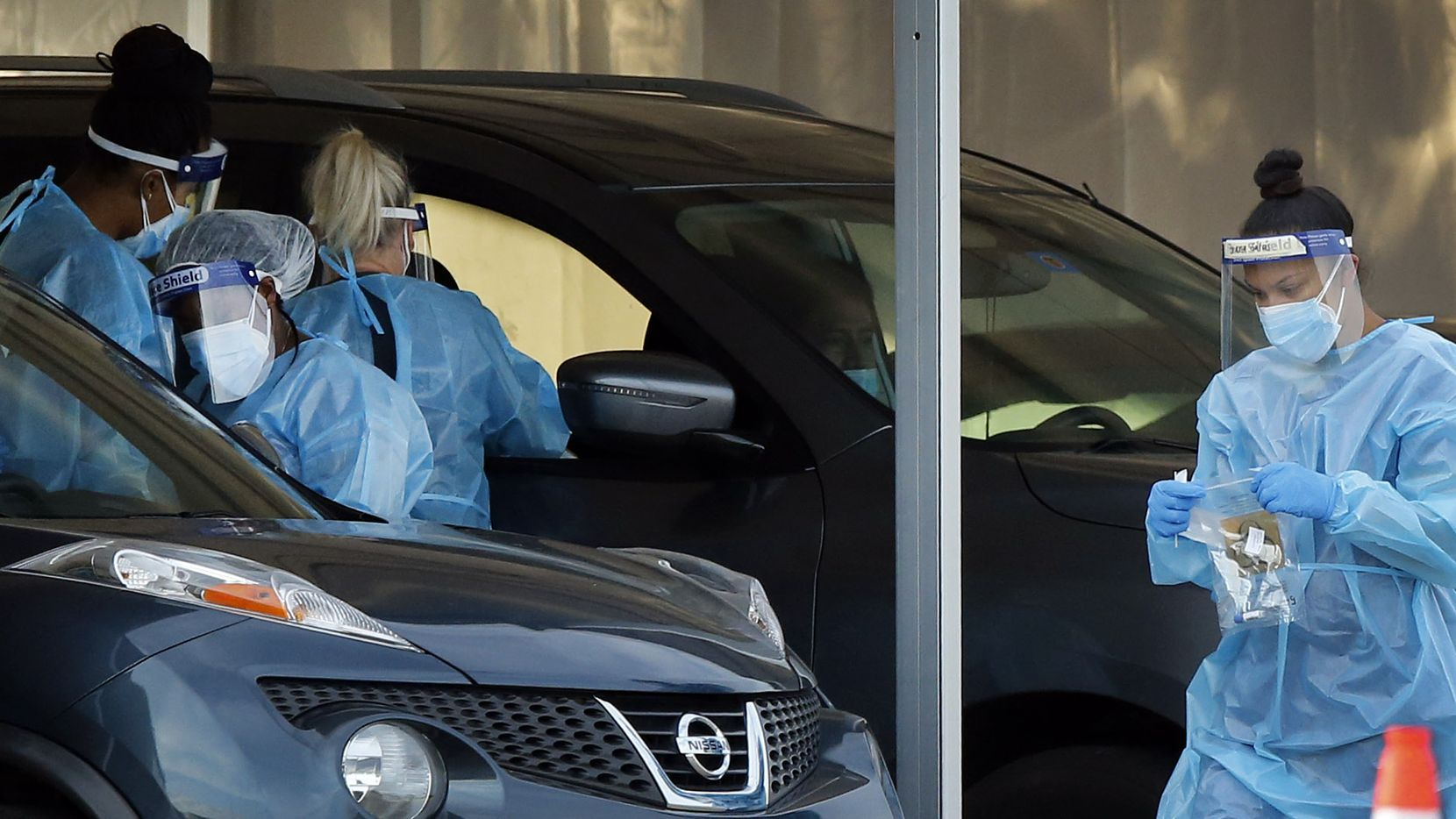Medical personnel conduct nasal swab tests at a drive-thru COVID-19 testing site on the Dallas College Eastfield Campus in Mesquite, Monday, August 3, 2020. (Tom Fox/The Dallas Morning News)