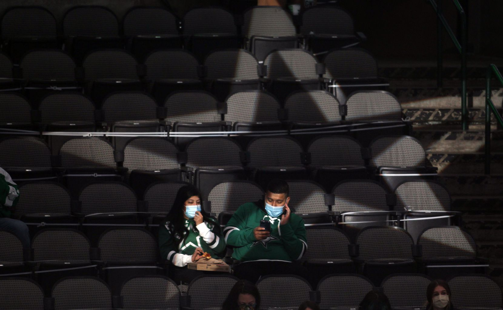 A couple of Dallas Stars fans are illuminated and framed by an illuminated star passing through the stands prior to the start of the Stars versus Nashville Predators contest. The two teams played their NHL game at the American Airlines Center in Dallas on January 24 , 2021. (Steve Hamm/ Special Contributor)
