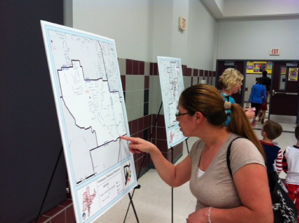 Erica Nava views maps of the elementary school attendance boundaries being proposed by the Denton school district for the 2014-15 school year at Crownover Middle School in Corinth.