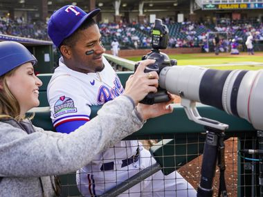 Texas Rangers infielder Andy Ibanez reviews photos of his 3-run home run on the back of the camera of team photographer Kelly Gavin during the eighth inning of a spring training game against the Chicago Cubs at Surprise Stadium on Thursday, Feb. 27, 2020, in Surprise, Ariz.