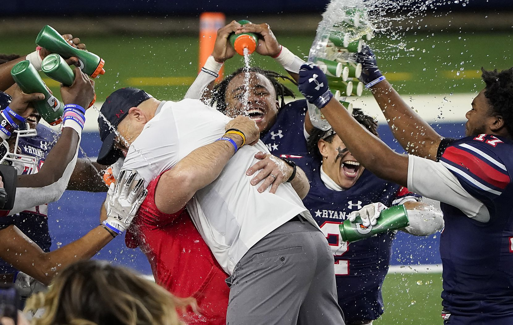 Denton Ryan head coach Dave Henigan hugs assistant coach Shane Tolleson as they are doused by their players in celebration of a 59-14 victory over Cedar Park to win the Class 5A Division I state football championship game at AT&T Stadium on Friday, Jan. 15, 2021, in Arlington, Texas. (Smiley N. Pool/The Dallas Morning News)