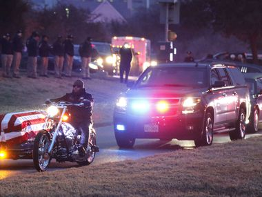Law enforcement officers saluted as a motorcycle carried Richardson police Officer David Sherrard after his funeral at Watermark Community Church in Dallas on Feb. 13, 2018. Sherrard was fatally shot at an apartment complex.
