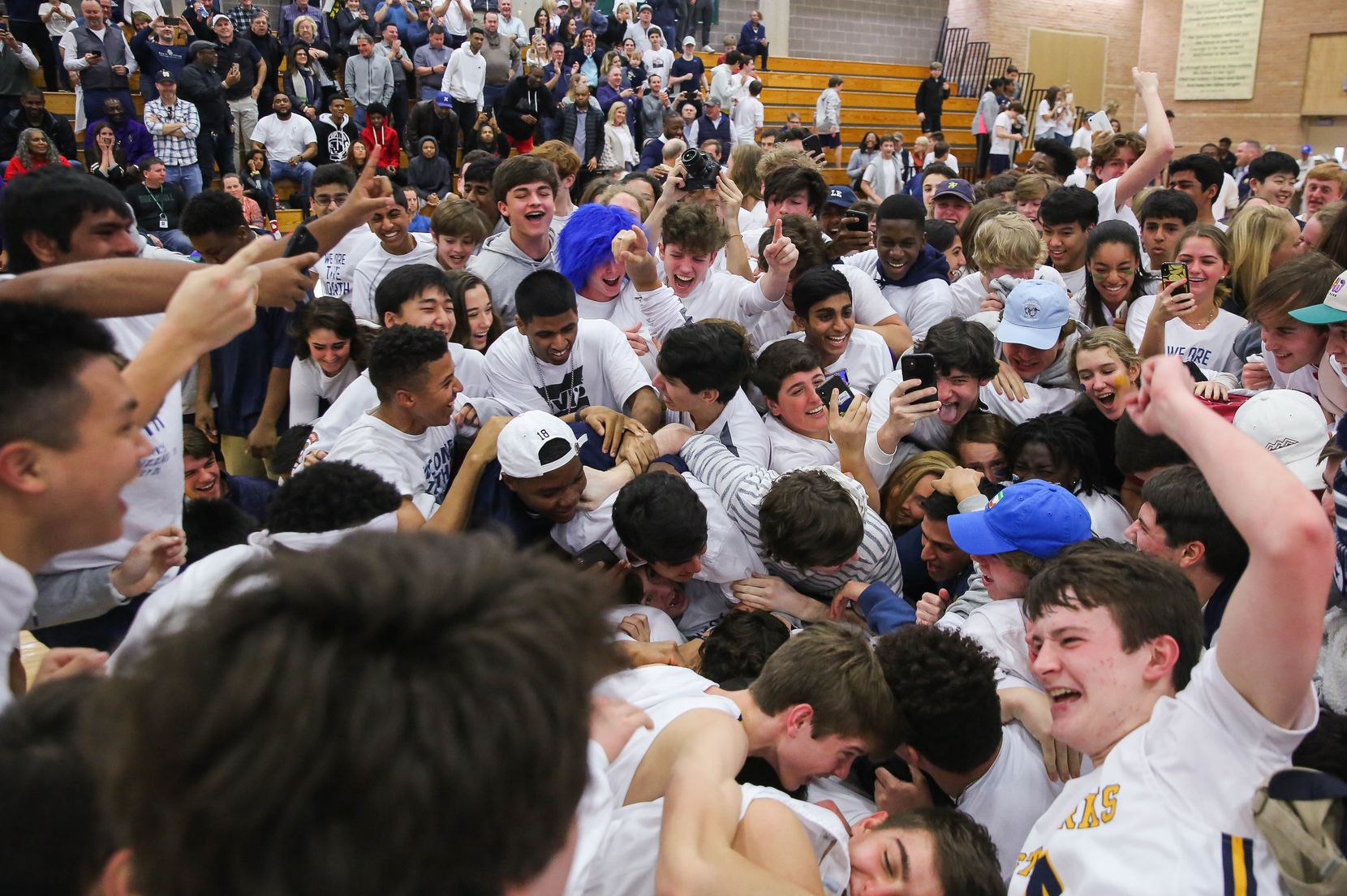 The St. Mark's student section dog pile the players after winning a SPC boys basketball championship game against Houston Christian on Feb. 15, 2020 held at The Greenhill School inAddison. St. Mark's won 85-57.