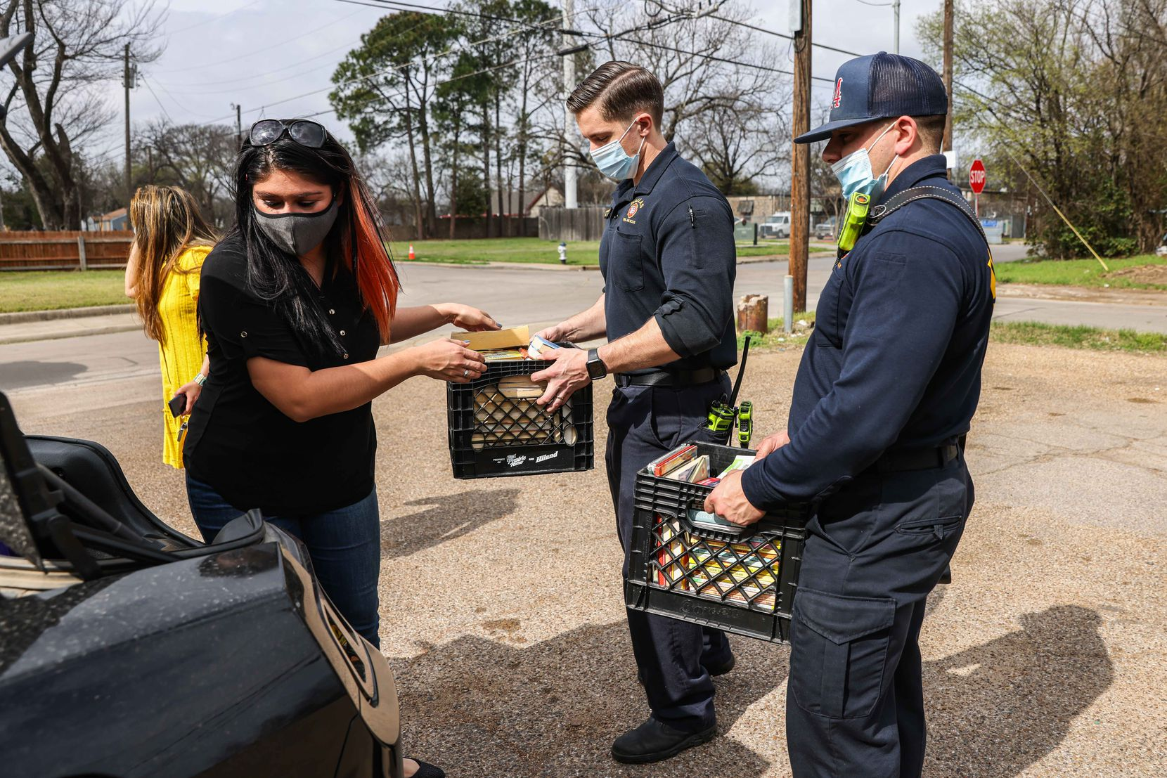 Aidee Lomeli of Fort Worth, enlists the help of firefighters Will Tabor and Richard Courts of Dallas Fire Station 24 to bring donated books to Allen's, a South Dallas grocery store, on Tuesday, March 16, 2021 (Lola Gomez / The Dallas Morning News)