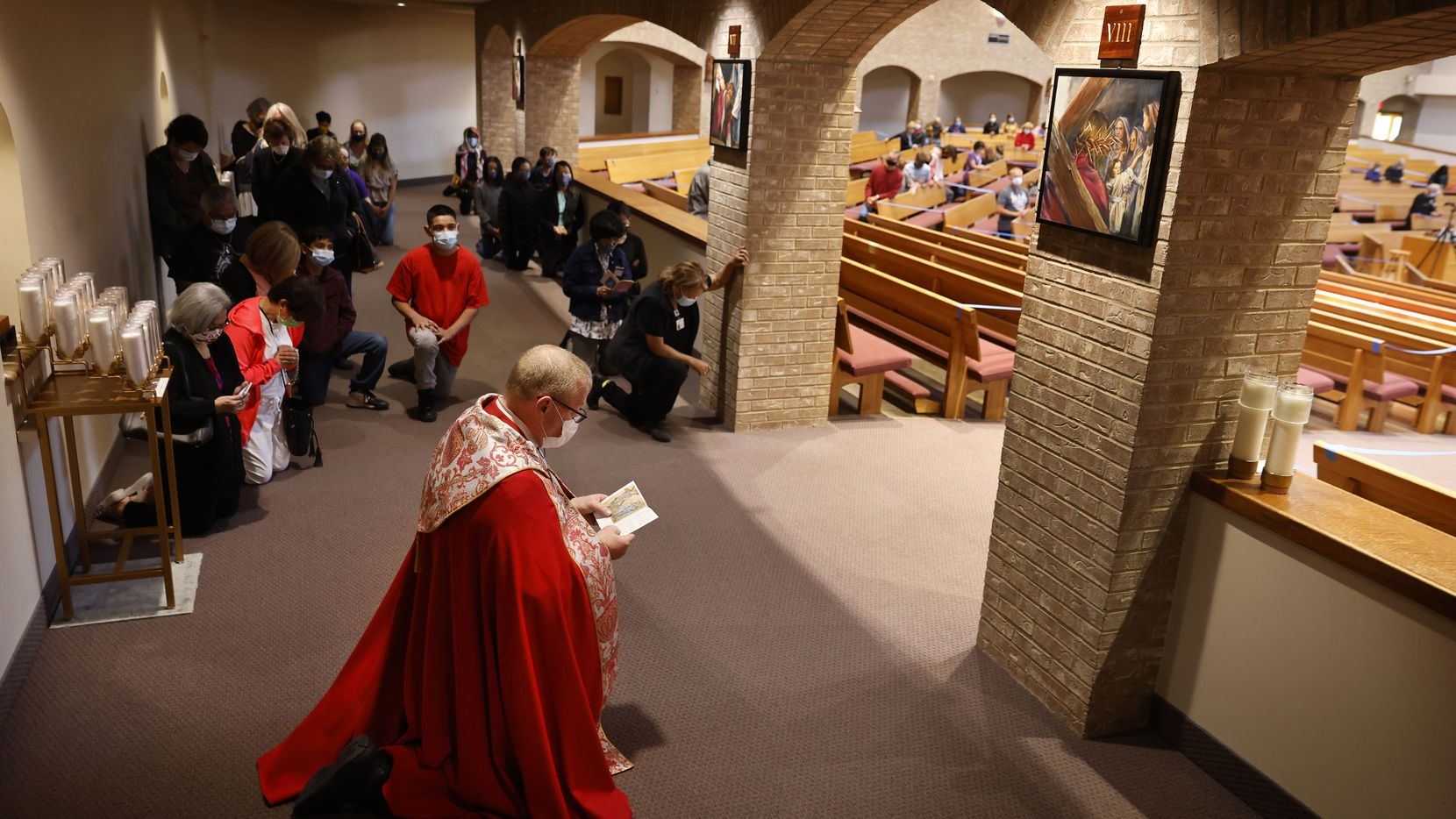 On Good Friday, Father Daniel Kelley kneels before the eighth station, Jesus meets the women of Jerusalem, as he leads a spiritual pilgrimage of the Stations of the Cross at St. Joseph Roman Catholic Parish in South Arlington, April 2, 2021.