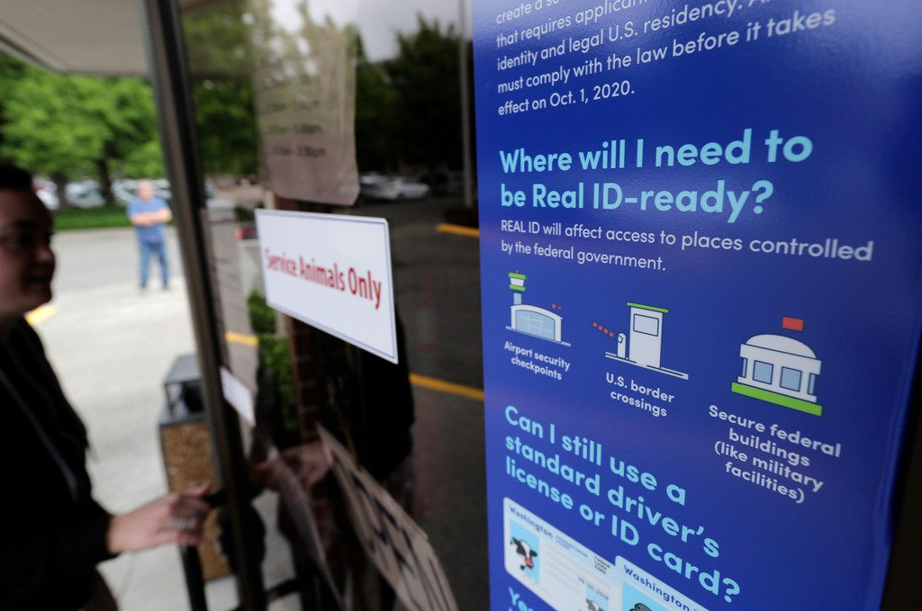 A customer opens the door of a Washington state Dept. of Licensing office in Lacey, Wash., Friday, June 22, 2018 next to a sign providing information about the requirements of Real ID.