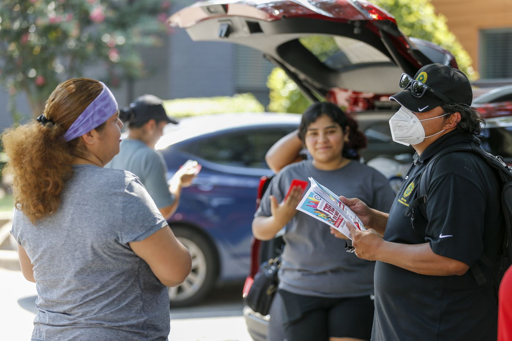 Armando Martinez, Dallas County Health & Human Services community liaison, speaks with residents about a back-to-school immunizations and COVID-19 vaccine clinic on Friday, July 30, 2021, in Dallas. (Elias Valverde II/The Dallas Morning News)