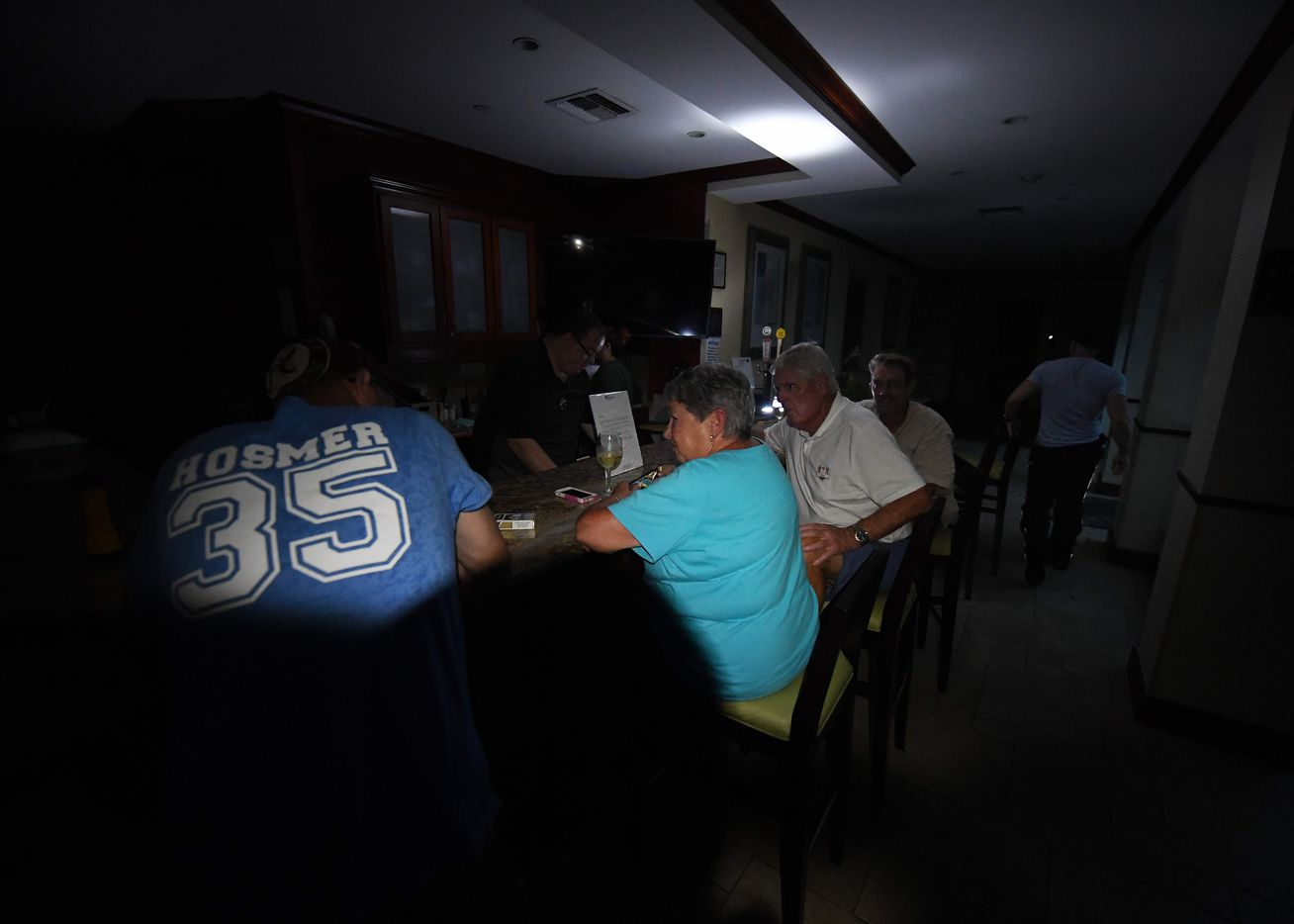 Local residents sit at the bar in the dark after a citywide power failure as Hurricane Harvey hit Corpus Christi, Texas, on August 25, 2017.   Harvey on Friday further intensified into a dangerous category four storm, just hours before it was due to slam into the Texas coast, US meteorologists said.