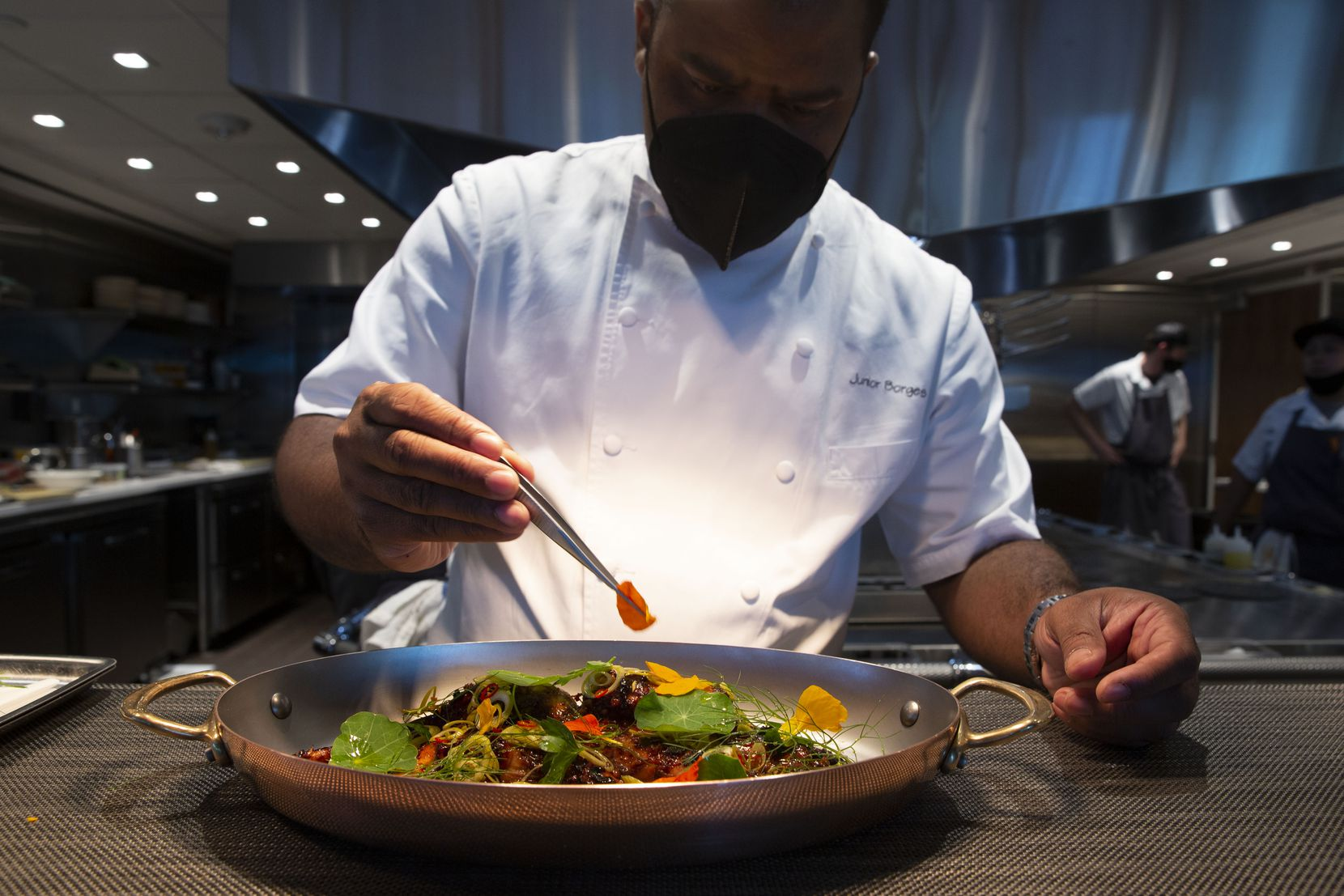Chef Junior Borges puts the final touches on the grilled octopus at Meridian restaurant, in The Village area of Dallas.