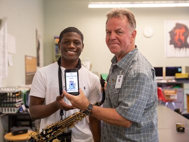 Donovan Spruiells and Donald Fabian pose with the Monster Musician Reader app at the Dallas Winds Summer Band Camp in the summer of 2019.
