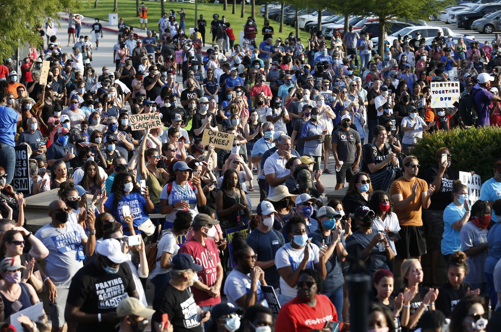 People clap after singing a song during a McKinney demonstration organized by Collin County churches Thursday.