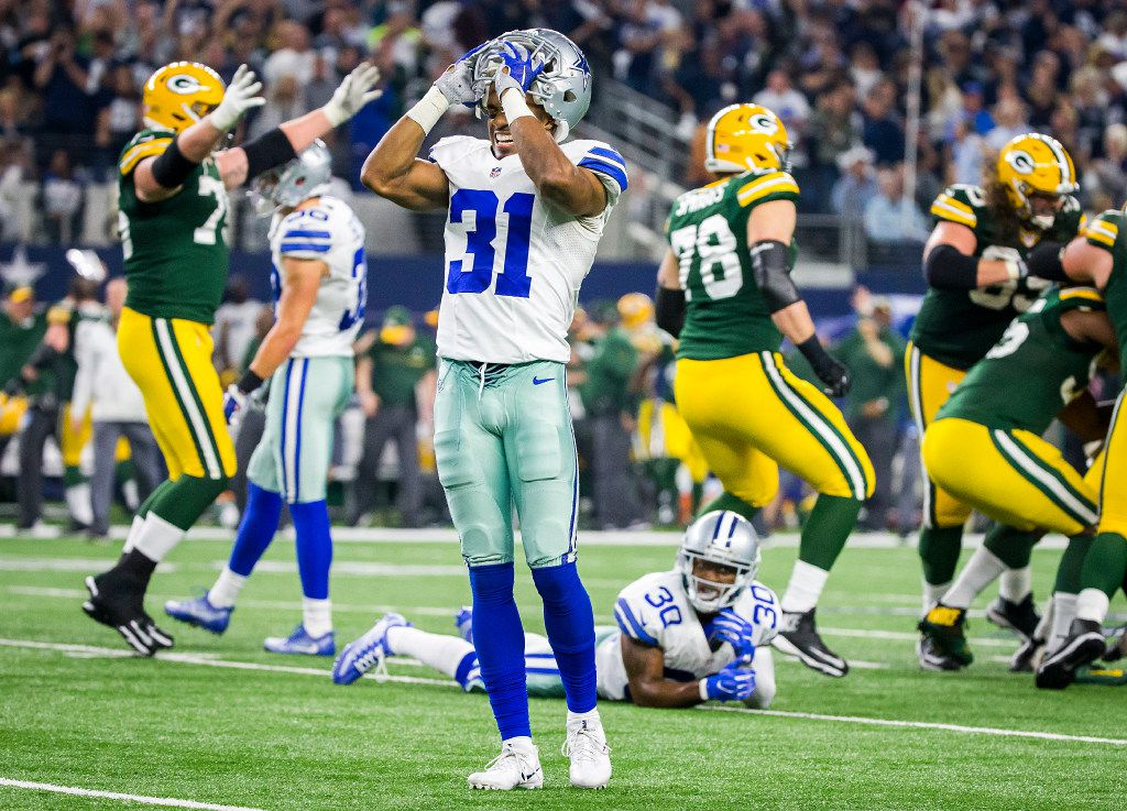 Dallas Cowboys free safety Byron Jones (31) and Dallas Cowboys cornerback Anthony Brown (30) react as Green Bay Packers players mob kicker Mason Crosby (2) after he kicked a game-winning 51-yard field goal on the final play of an NFC divisional round playoff game at AT&T Stadium on Sunday, Jan. 15, 2017, in Arlington. (Smiley N. Pool/The Dallas Morning News)