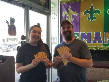 Ciara Ronasi, an employee at Po' Melvin's, and Mark McKee hold gift cards inside the restaurant.