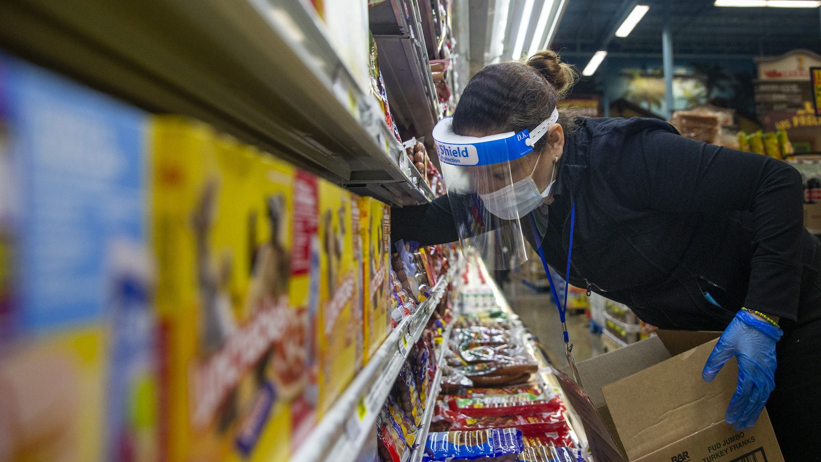 Rebecca Sierra restocks packaged meats at the El Rancho Supermercado on Gaston Avenue in Dallas during the height of the pandemic in April. The store has been taking precautionary measures against the spread of COVID-19, said store manager Eugenio Osorio.