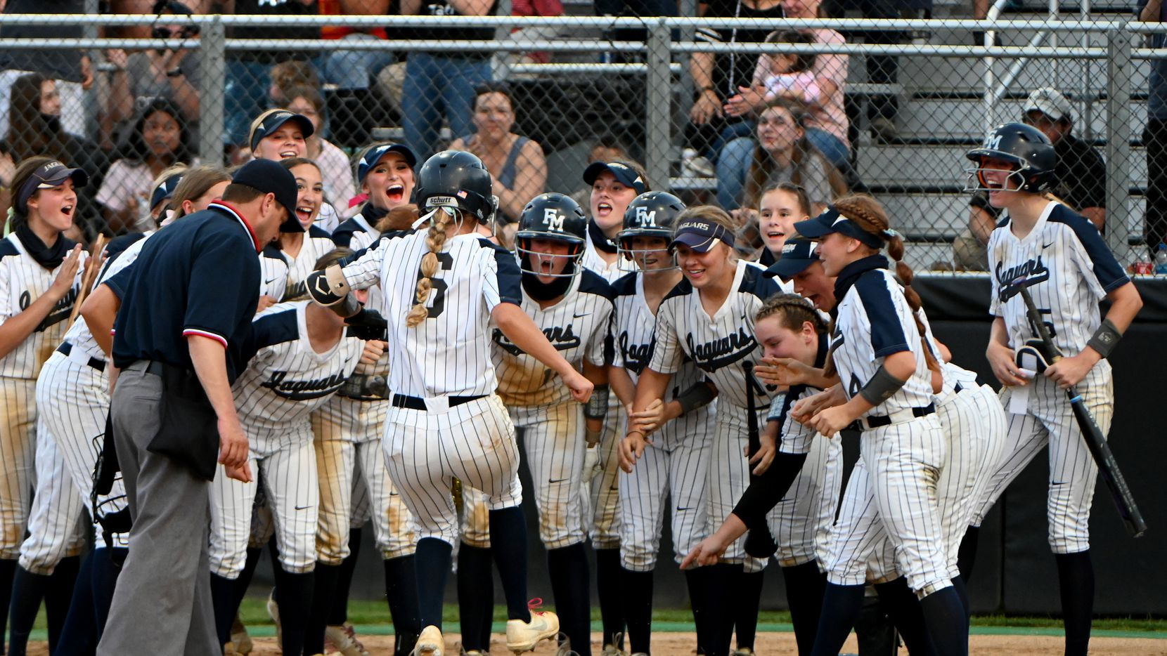 Flower Mound players wait at home plate to celebrate with McKenna Andrews (8) after her two-run home run during game 1 of the Class 6A Region I final softball series between Prosper and Flower Mound, Wednesday, May 26, 2021, in Flower Mound, Texas.