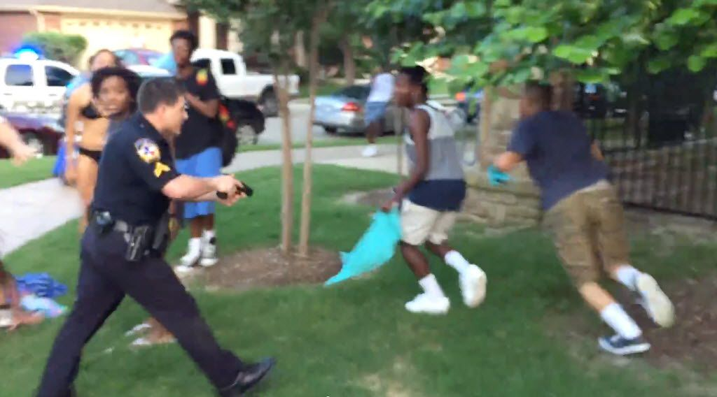 Former McKinney police Officer Eric Casebolt, with gun drawn, chases two men who had come close as he tried to arrest a black teen female in June 2015.